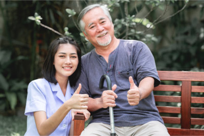 nurse with patient sitting on bench doing thumbs up