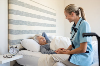 elderly woman in a bed with her nurse