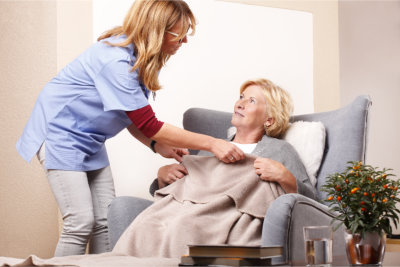 nurse giving a blanket to the senior