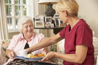 caregiver serving meal to the old woman