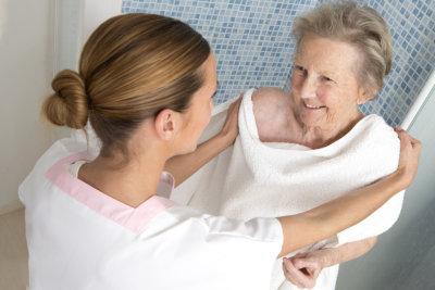 caregiver assisting senior woman in bathing